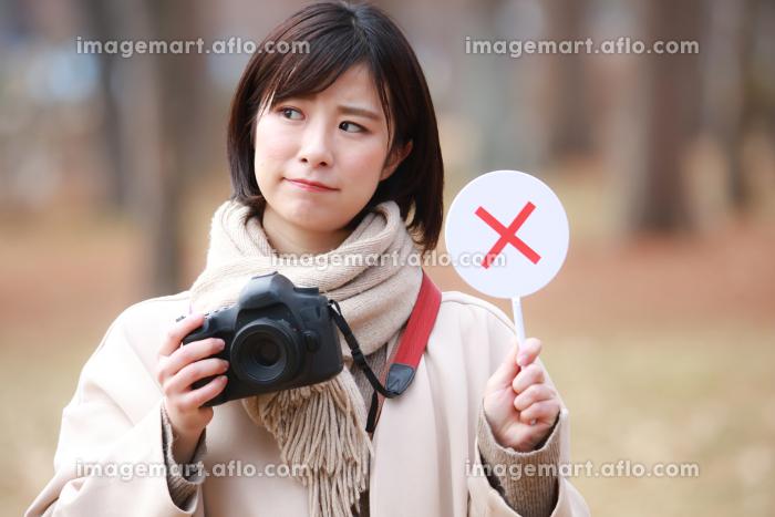一眼レフカメラと×札を持つ女性の販売画像