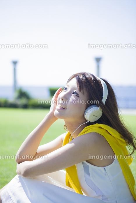 芝生に座りヘッドフォンで音楽を聴く女性
