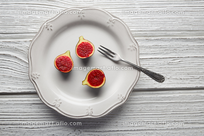 figs raw cutted fig fruits on white plate and wooden tableの販売画像