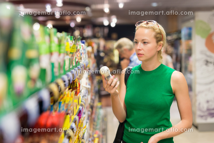 Woman shopping personal hygiene products at supermarket.の販売画像