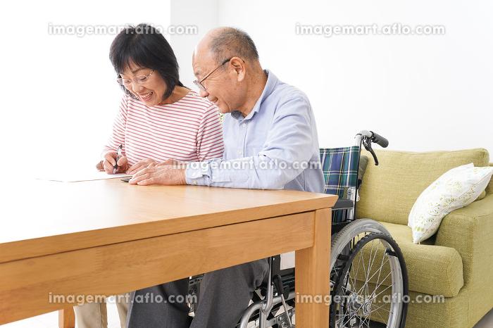 契約をする高齢の夫婦の販売画像