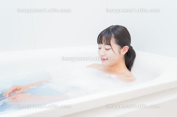 お風呂でお湯に浸かる若い女性の販売画像