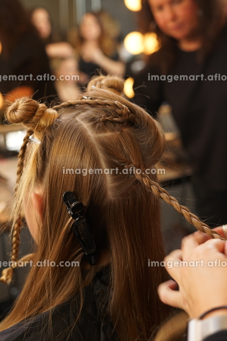 Hairstylist plaiting young woman's hair for a fashion show during NYFWの販売画像