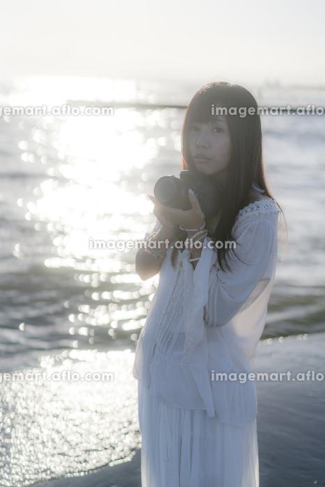海辺でカメラを構える女性
