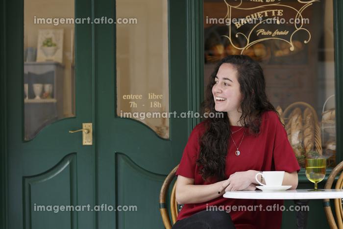 街角のカフェでくつろぐ外国人の若い女性の販売画像