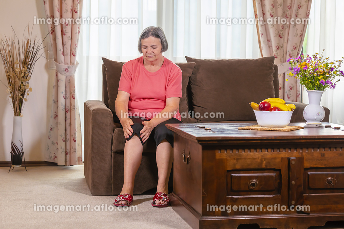 Elderly woman suffering from pain in knee at homeの販売画像