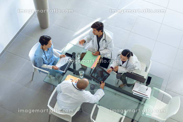 High angle view of diverse medical team discussing with each other at the table of conference room in hospitalの販売画像
