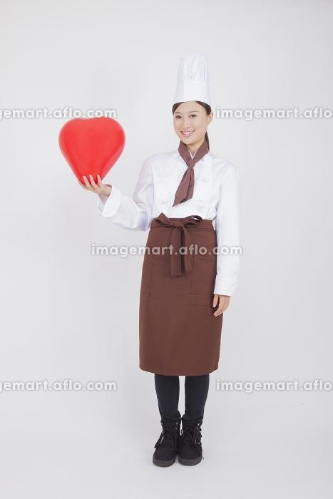 ハートの風船を持つ女性料理人