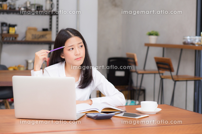 Asian young woman working online with laptop and think project f
