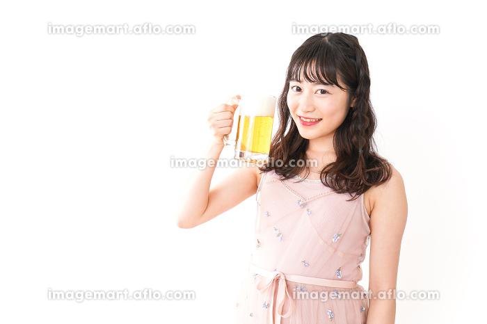 グラスを持ちビールを飲む若い女性の販売画像
