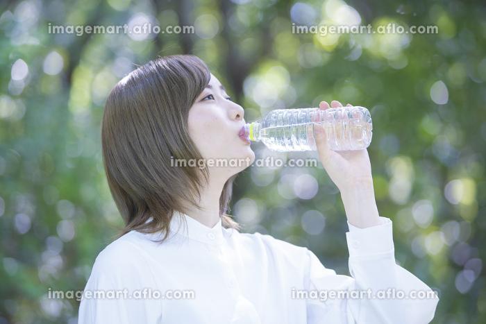 屋外で水を飲む女性の販売画像