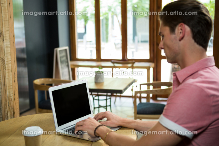 Man using laptop at table in coffee shop