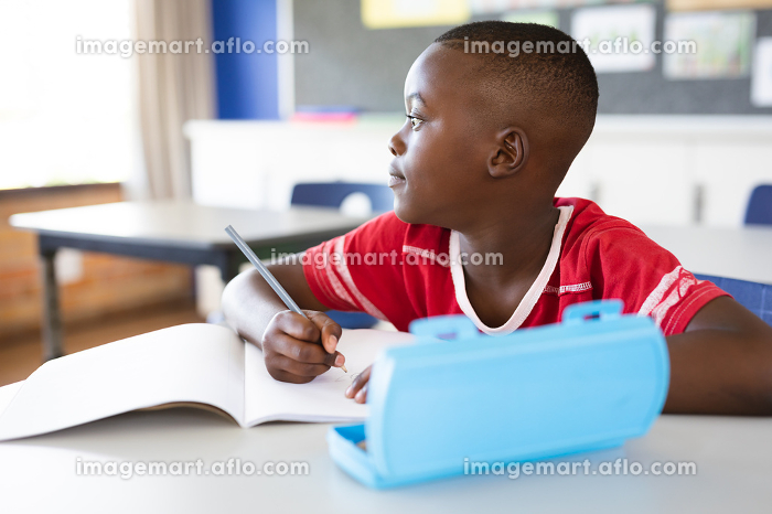African american boy studying while sitting on his desk in the class at school. school and education conceptの販売画像