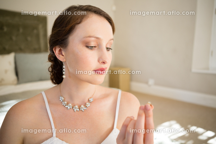Beautiful bride looking wedding ring while sitting on bedの販売画像