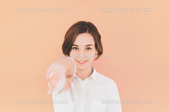 指をさす若い女性(カラフルな色の背景)の販売画像