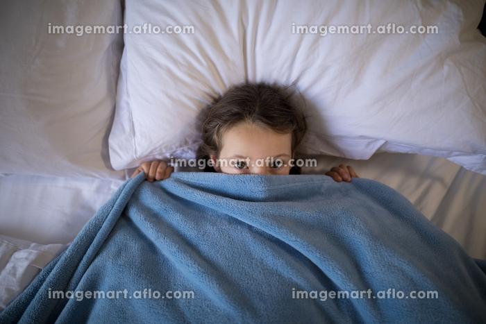 Girl covering her face under the blanket while lying on bed