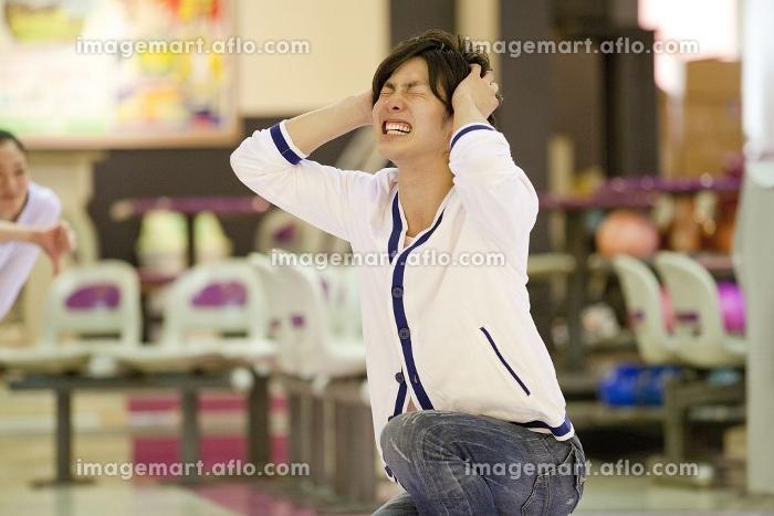 ボウリングをして頭を抱える男性の販売画像