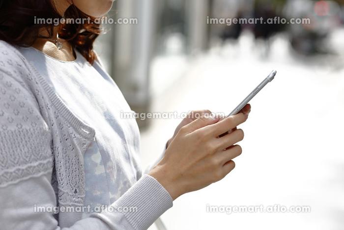 街中でスマートフォンを見る若い女性の販売画像