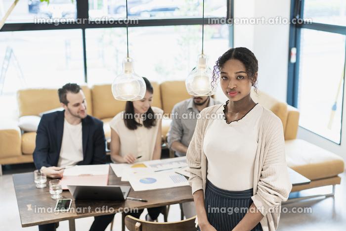 オフィスでポーズをするビジネスウーマンと国際色豊かなビジネスチームの販売画像