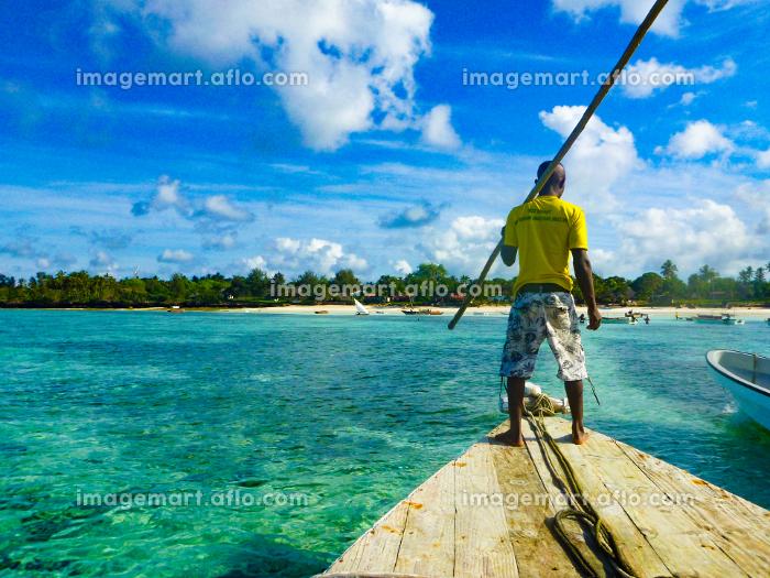 タンザニア・ザンジバル島の海と船を漕ぐアフリカ人の販売画像