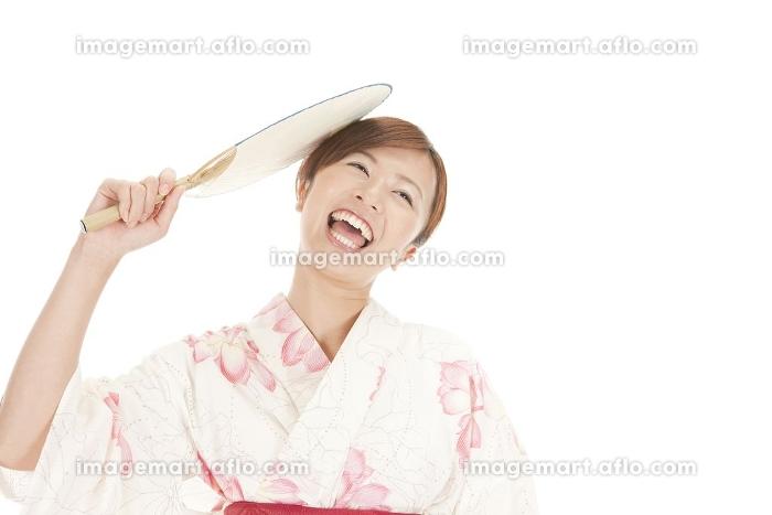 団扇で自分の頭をたたく浴衣女性の販売画像