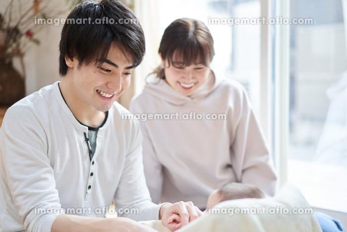 赤ちゃんと遊ぶアジア人の夫婦の販売画像