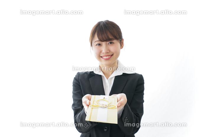 祝儀袋を渡すスーツ姿の女性の販売画像