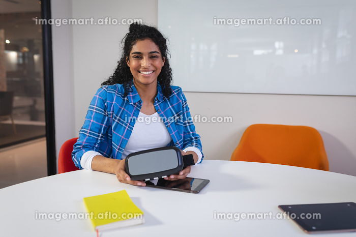 Happy mixed race businesswoman sitting at work holding virtual reality set. independent creative design business.の販売画像
