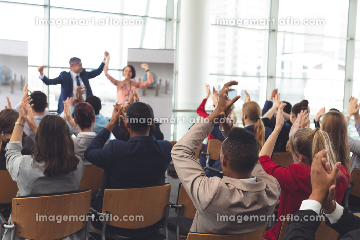Rear view of diverse business people applauding and celebrating while they are sitting in front of multi-ethnic business coworkers at business seminar in office buildingの販売画像