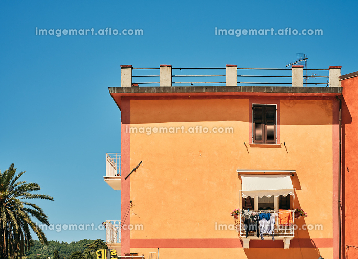 Orange building with small balcony in summerの販売画像