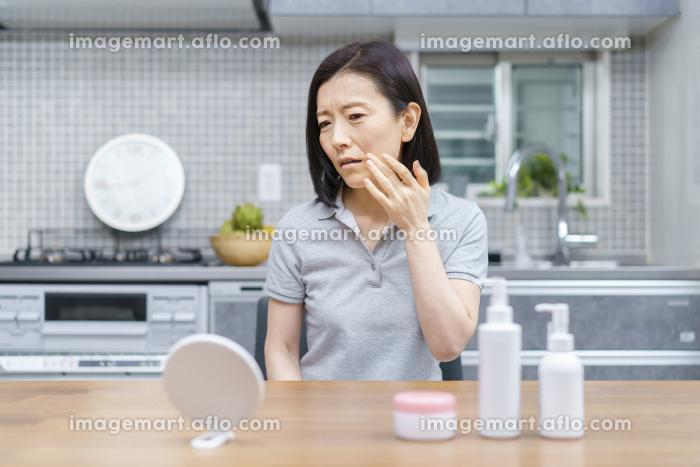 不安な表情で肌の状態を確かめる中年女性の販売画像