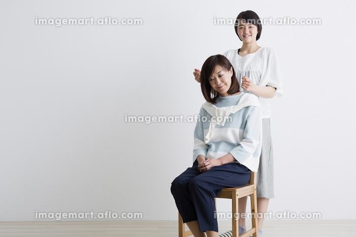 母親の肩をたたく娘の販売画像