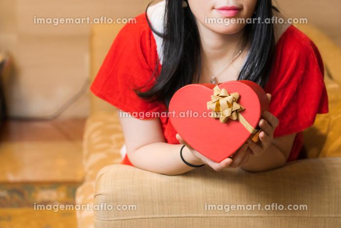 ハート型のプレゼントボックスを持ったサンタクロース姿の女性の販売画像