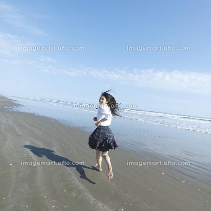 砂浜を走る女子高生