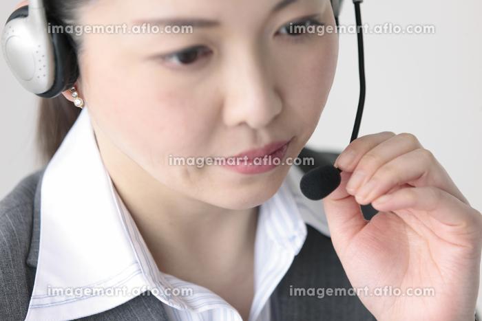 インカムをつけたビジネスウーマンのアップの販売画像