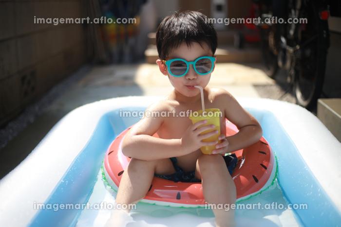プールで飲み物を飲む男の子の販売画像