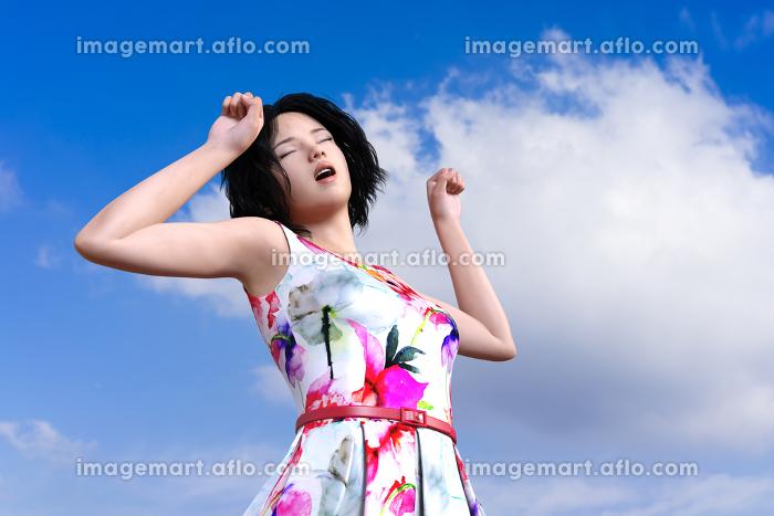 青空の下で花がプリントされた白いワンピースを着た黒髪の女の子が目をつむり身体を伸ばしている