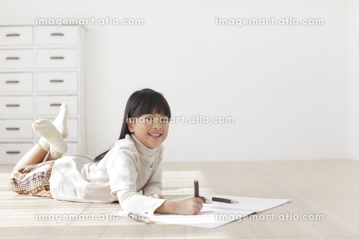 スケッチブックに色鉛筆で絵を描く女の子の販売画像