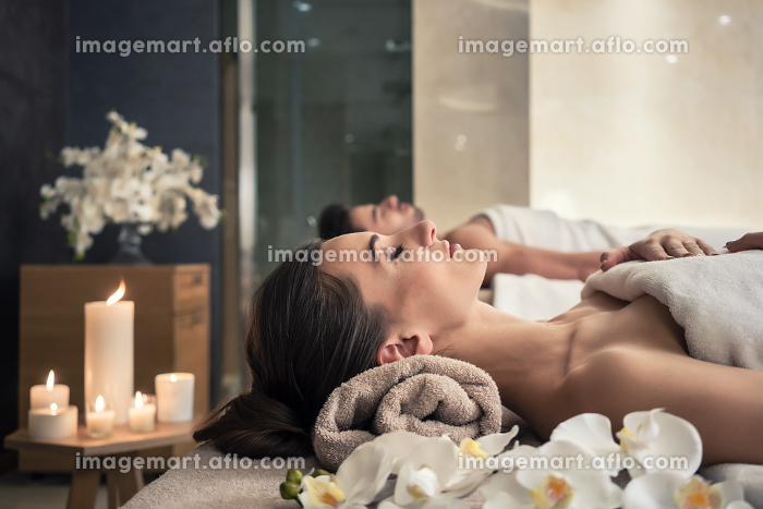 Man and woman lying down on massage beds at Asian wellness cente