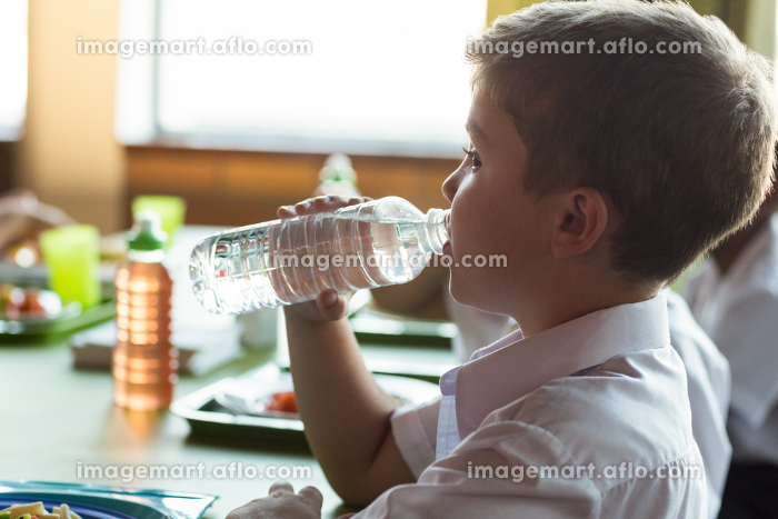 Close-up of schoolboy drinking waterの販売画像
