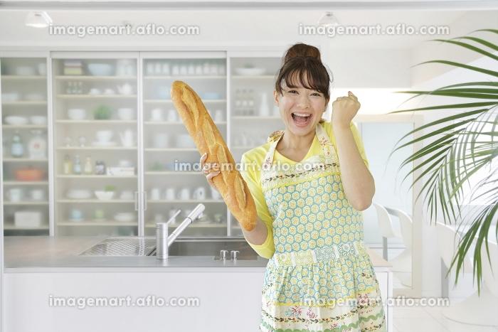 パンを持ちガッツポーズをするエプロン姿の主婦の販売画像