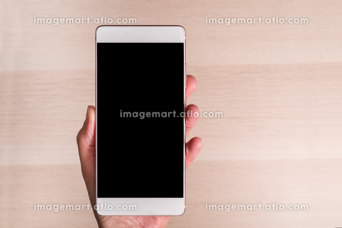 hand holding smartphone with blank screen isolated on wooden bacの販売画像