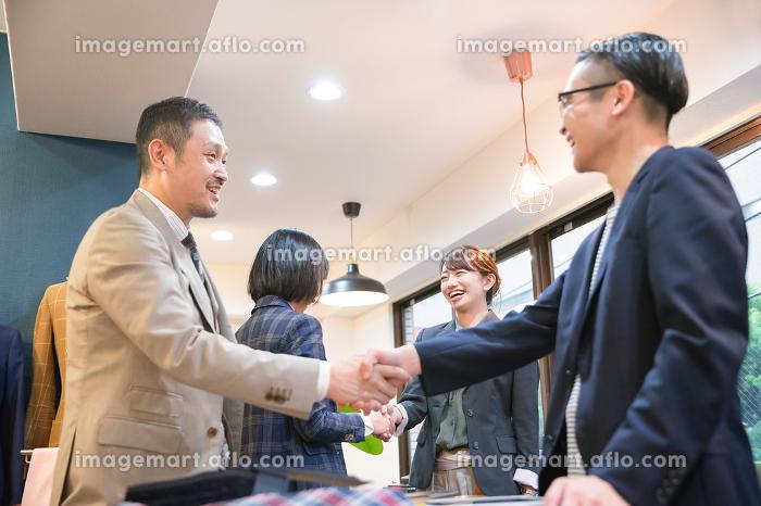 笑顔で握手をする4人の人物の販売画像