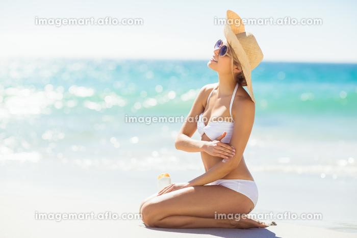 Woman applying sunscreen on her handの販売画像