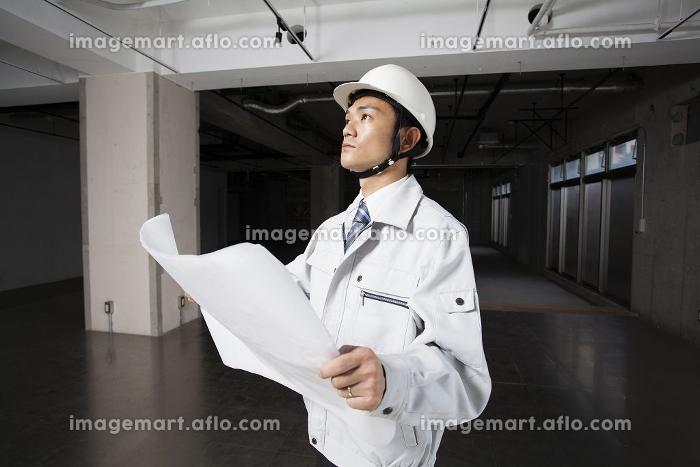 図面を広げる現場監督の販売画像