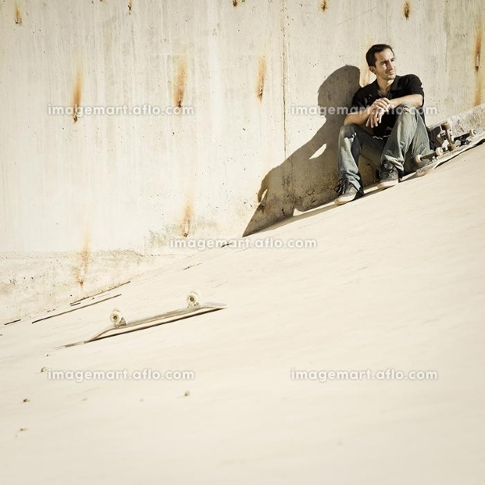 Skateboarder sitting on concrete slopeの販売画像
