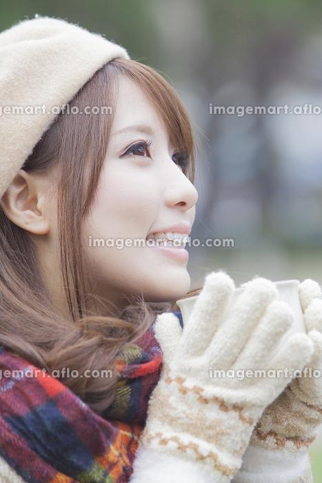 マフラーをしてマグカップを持つ手袋をした女性の販売画像