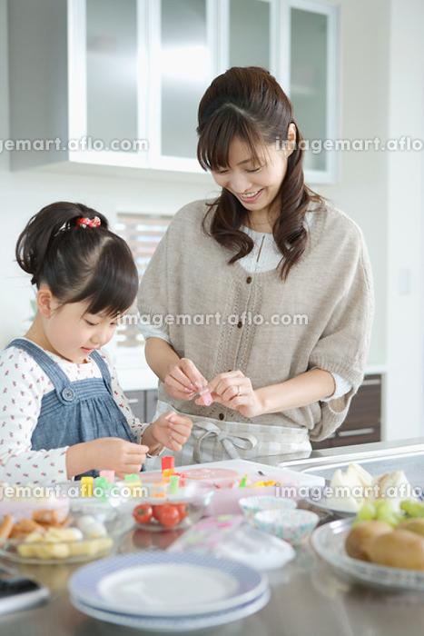 料理をするお母さんと娘の販売画像