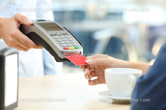 Woman paying with credit card reader in a barの販売画像