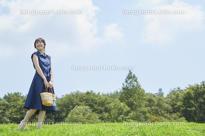 青空の下を歩く日本人女性の販売画像